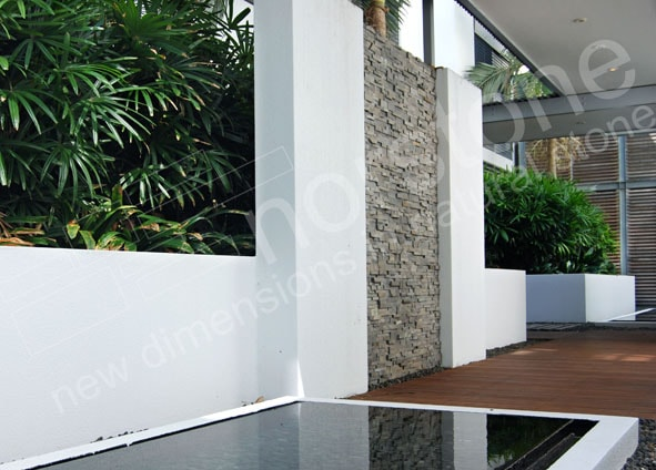 Norstone Charcoal Rock Panels used as a feature wall in a modern designed outdoor space with reflecting pond