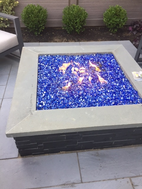 Norstone Aksent Modern Stone Cladding in Ebony Color on a gas firepit with bright blue glass media