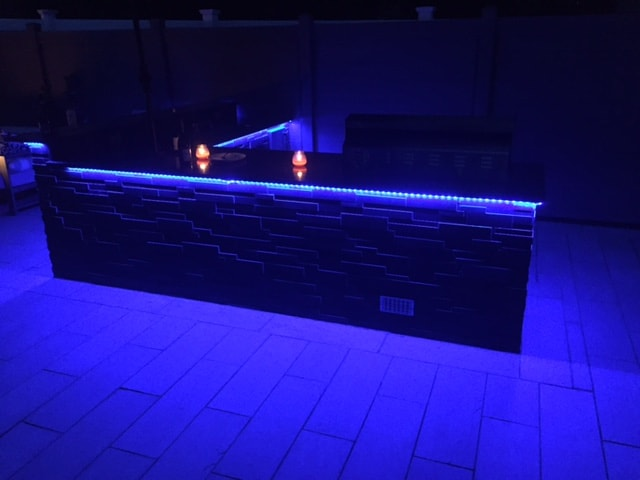 Norstone Aksent Modern Stone Cladding in Ebony Color on an Outdoor Kitchen with undermounted blue LED lighting