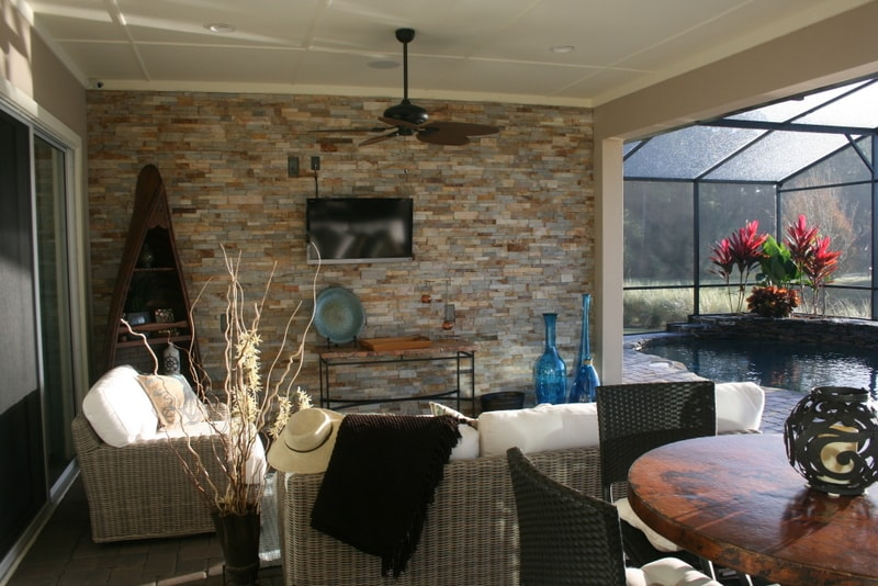Norstone Aztec Stacked Stone Veneer used on an outdoor feature wall in a small screened in lanai with outdoor lounge furniture and an outdoor television