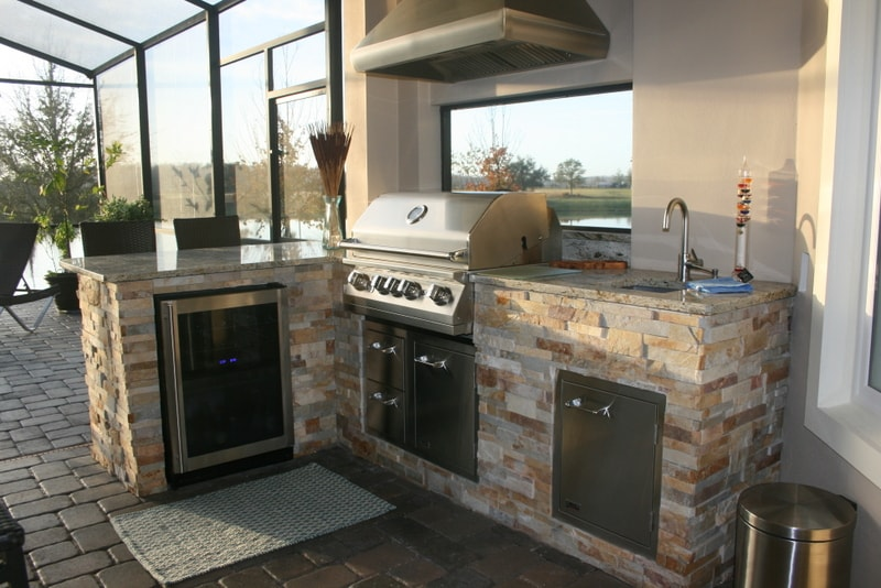 Norstone Aztec Stacked Stone Panels used on the base of an outdoor kitchen in Florida with grill, sink, and fridge