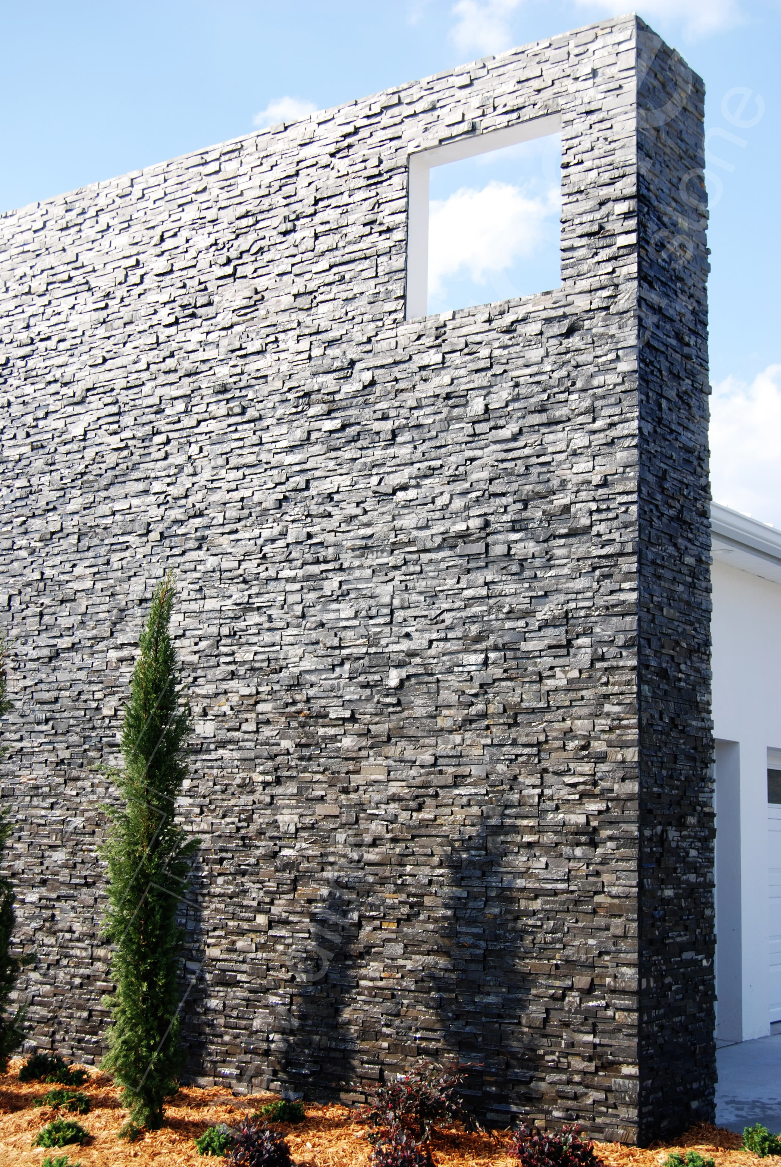 Norstone Charcoal Rock Panel thin stone veneer system used on a two story exterior feature wall in Florida
