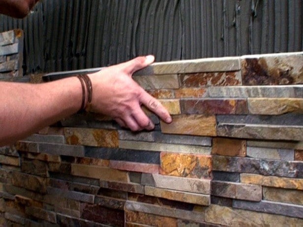 Thin stone veneer panel system units being installed on a wall using thinset