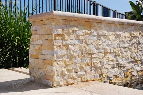 Norstone Finger Joint Corner Units shown in Ivory covering two outside corners on an exterior landscape wall with Travertine Cap