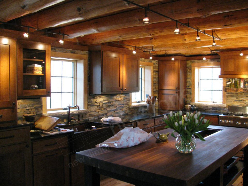 Norstone Ochre Blend Rock Panels on a Rustic Kitchen Backsplash with a large butcher block island and a ceiling with exposed natural log beams