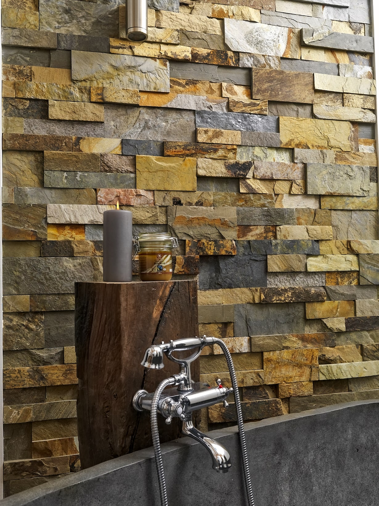 Norstone Ochre XL Stacked Stone on a bathroom feature wall showing a close up of vintage tub hardware