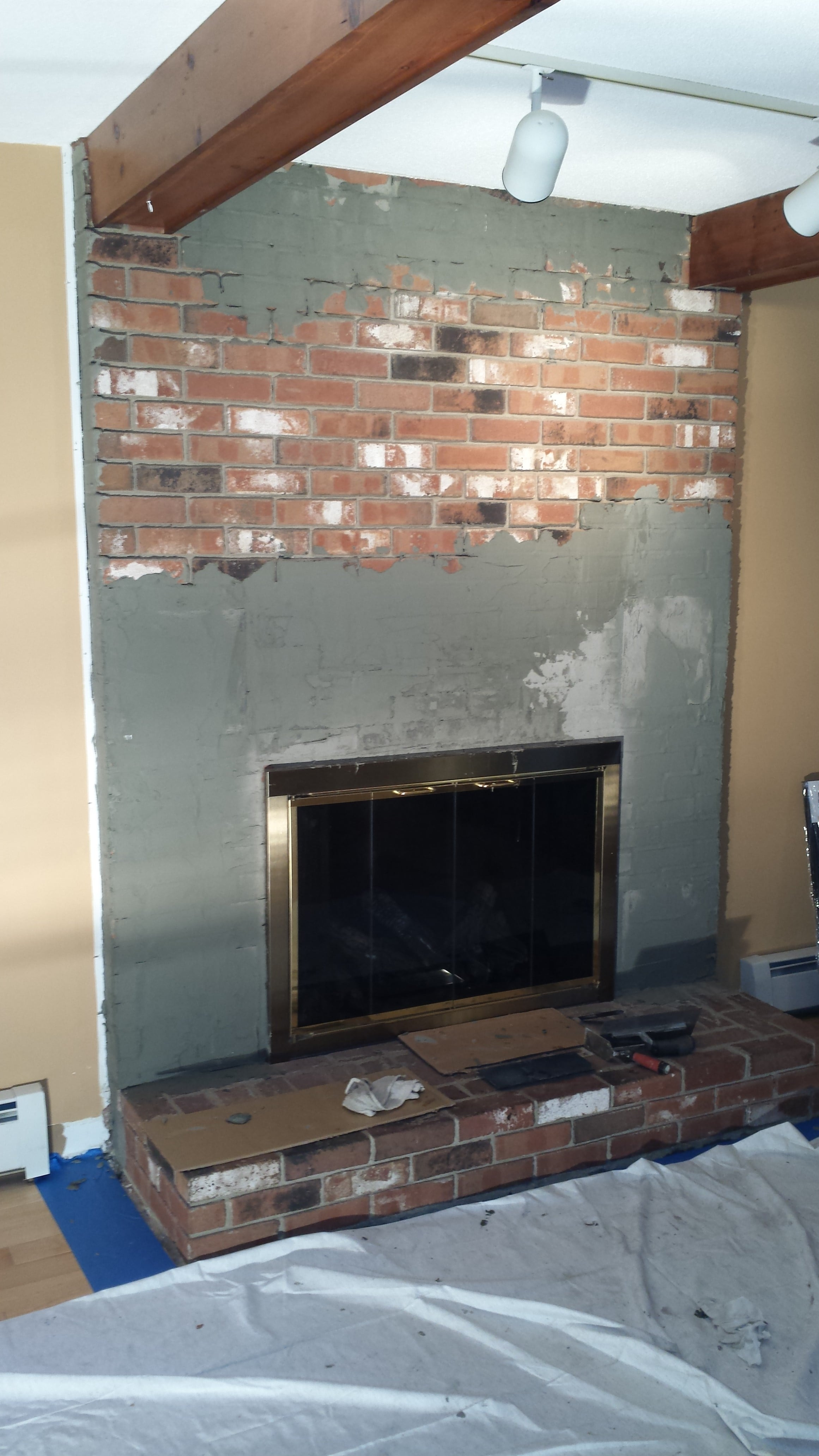 Old brick fireplace receiving a masonry skim coat to prep it for installation of Norstone Aztec XL Stone Veneer