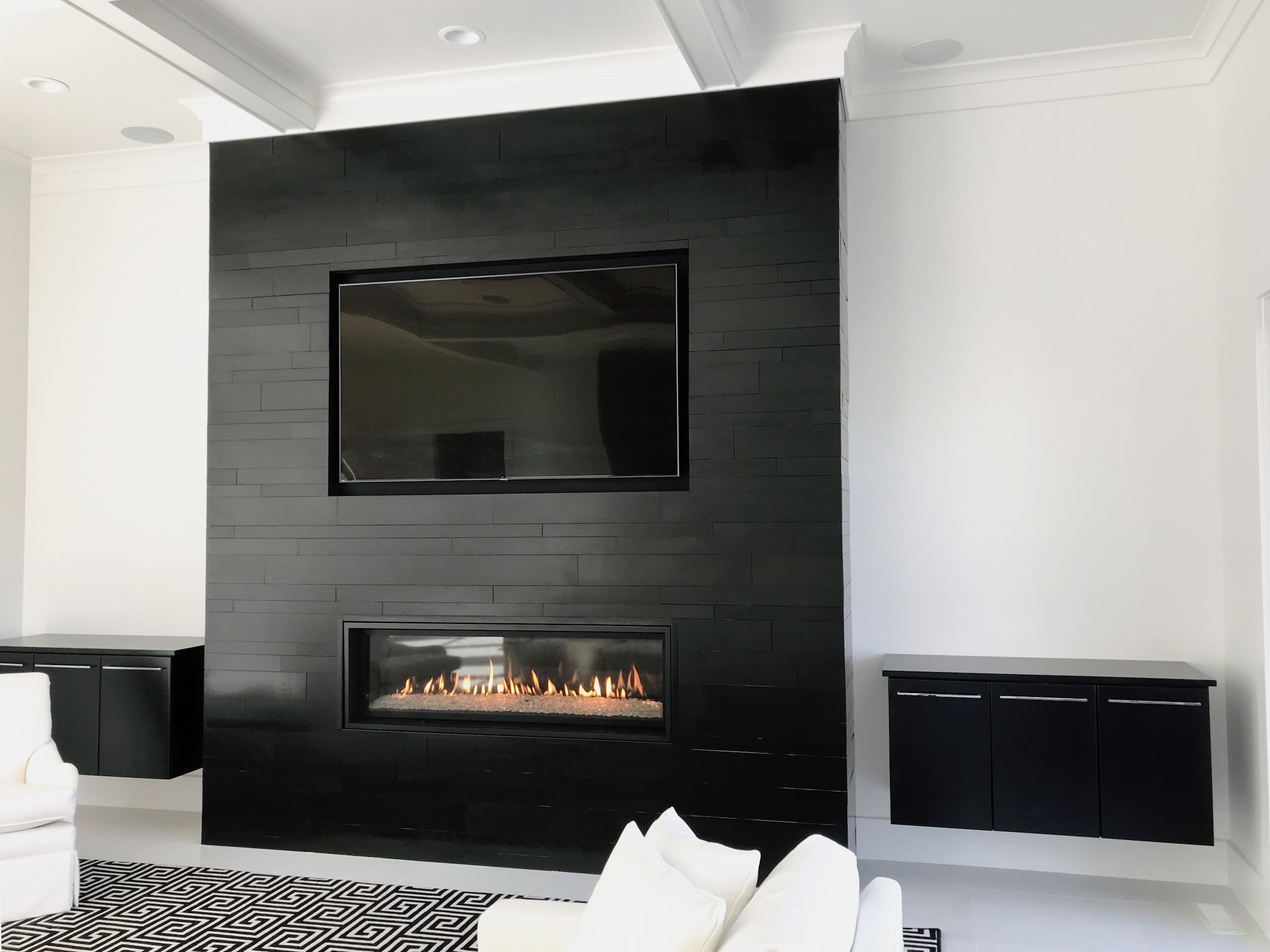 Norstone Planc Large Format Tiles in Ebony installed on a modern fireplace with linear gas insert and tv recess