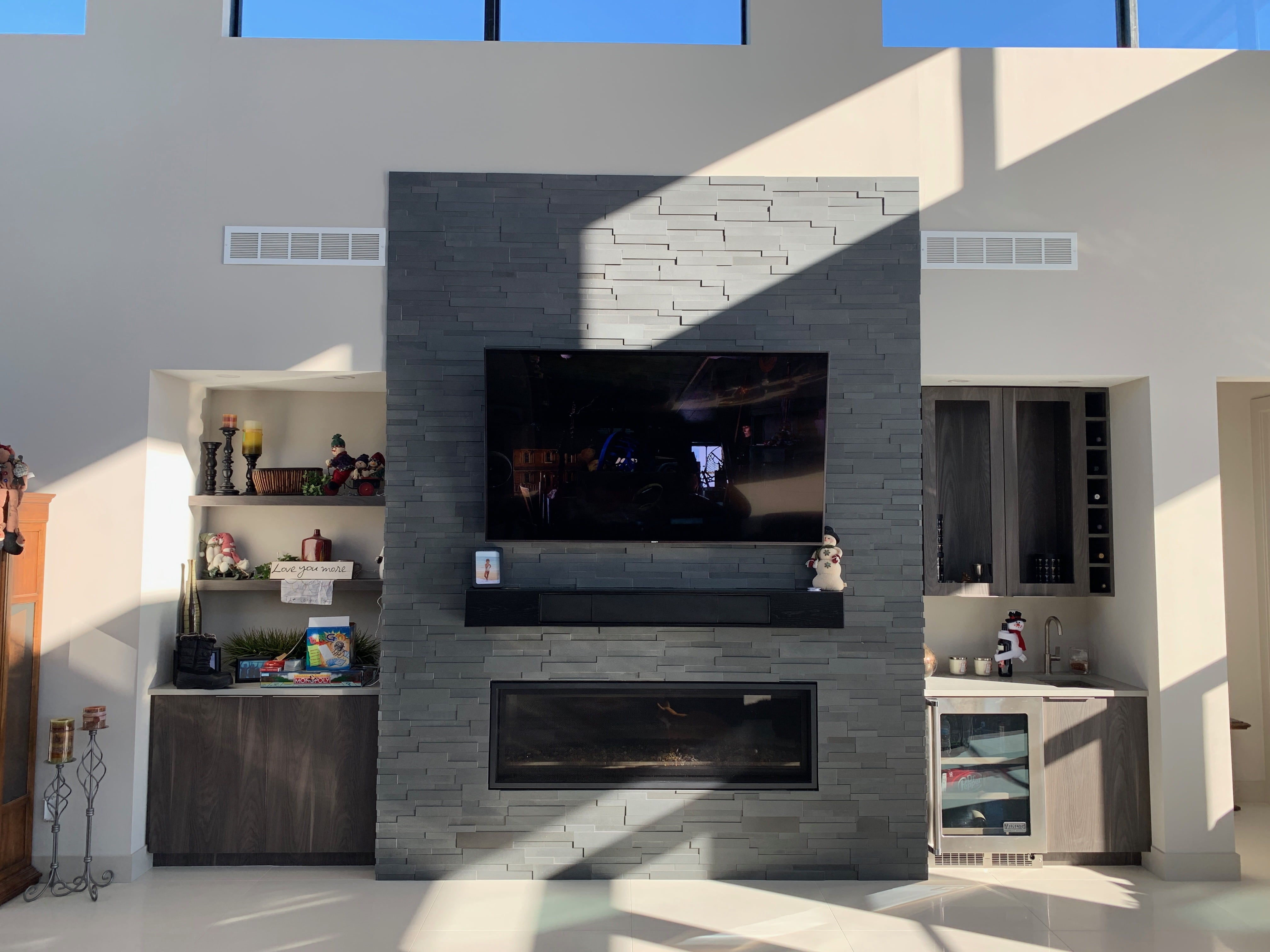 Norstone Aksent 3D Stone Panels in Ash Grey used on a modern fireplace with a large tv mounted above a linear gas insert