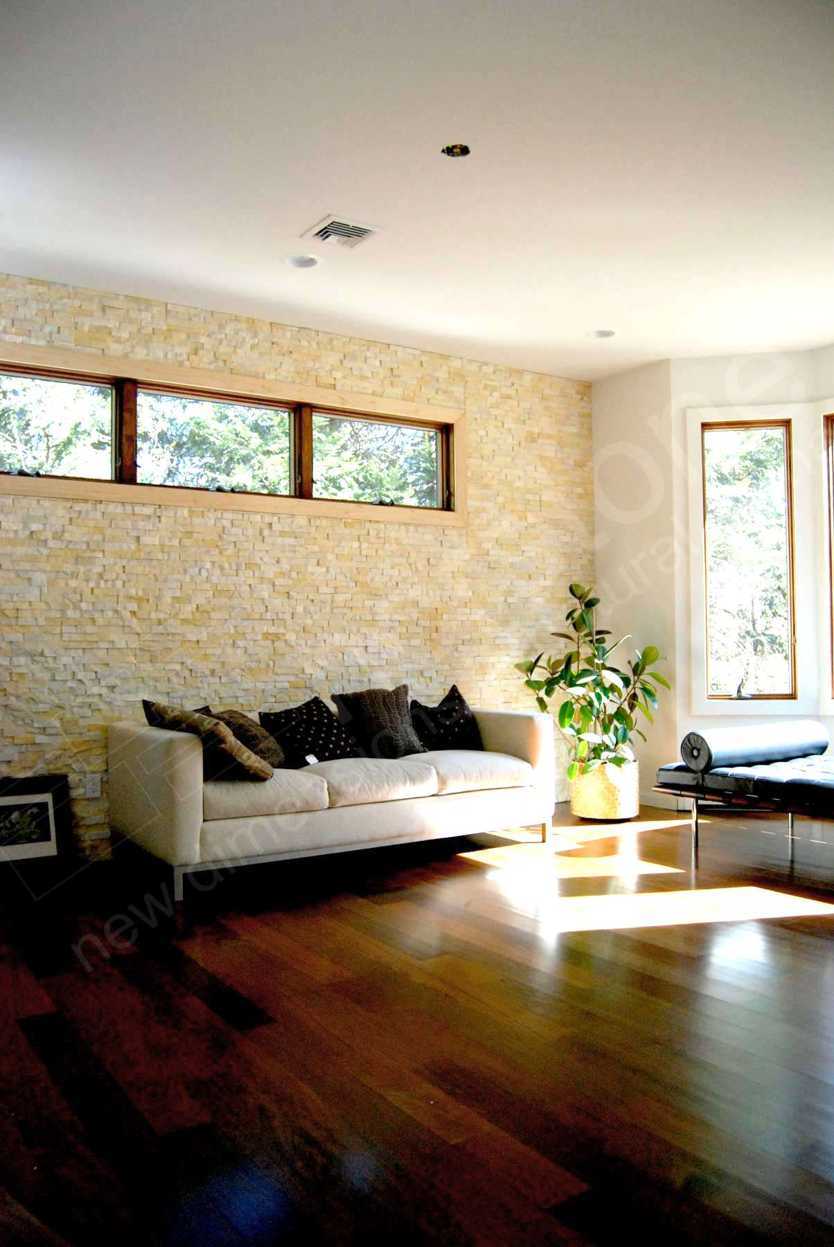 Natural Stone Feature Wall of Norstone Ivory Rock Panels with low slung couch and large window in a suburban NJ home for improved Indoor Air Quality