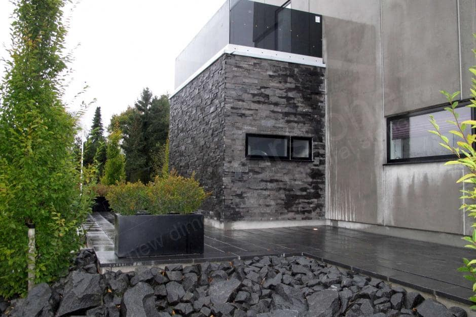 Norstone Charcoal XL Stone Veneer Panel used on the exterior of a residential home on a bump out with an open air terrace on the flat roof above it