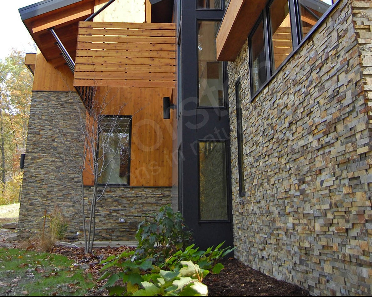 Exterior stacked stone residential project where the stone terminates into a landscaping bed to minimize the appearance of spalling stones