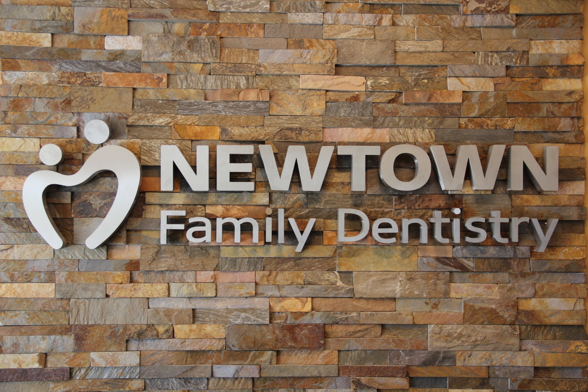 Norstone Ochre XL stacked stone feature wall with stainless steal signage in a Dentist Office in Delaware