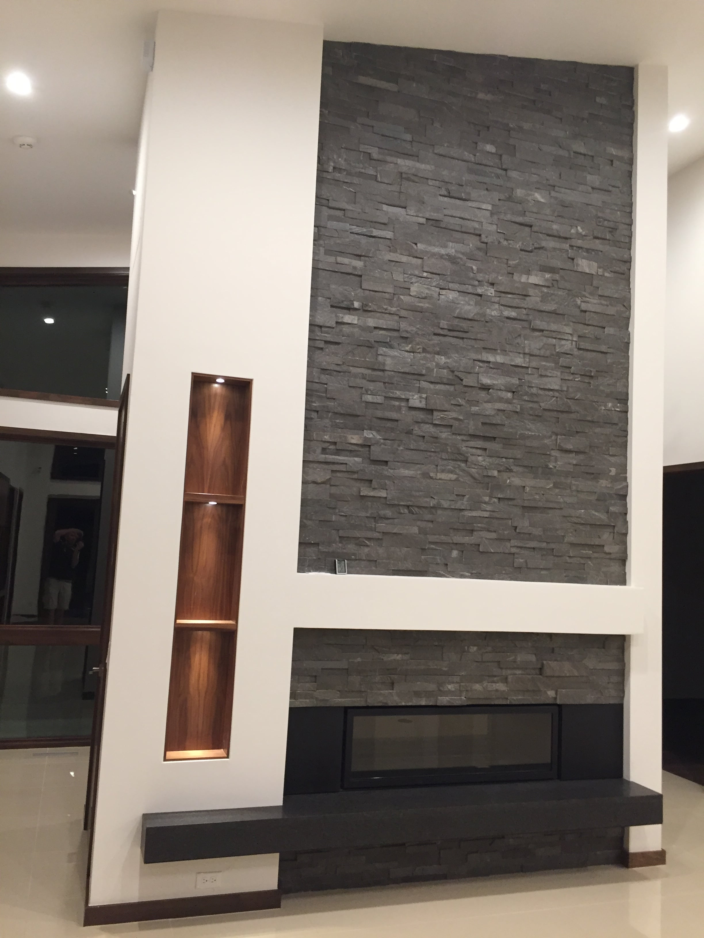 Norstone Charcoal Stacked Stone Rock Panels on a Floor to Ceiling Fireplace in a mid centry Modern styled living room