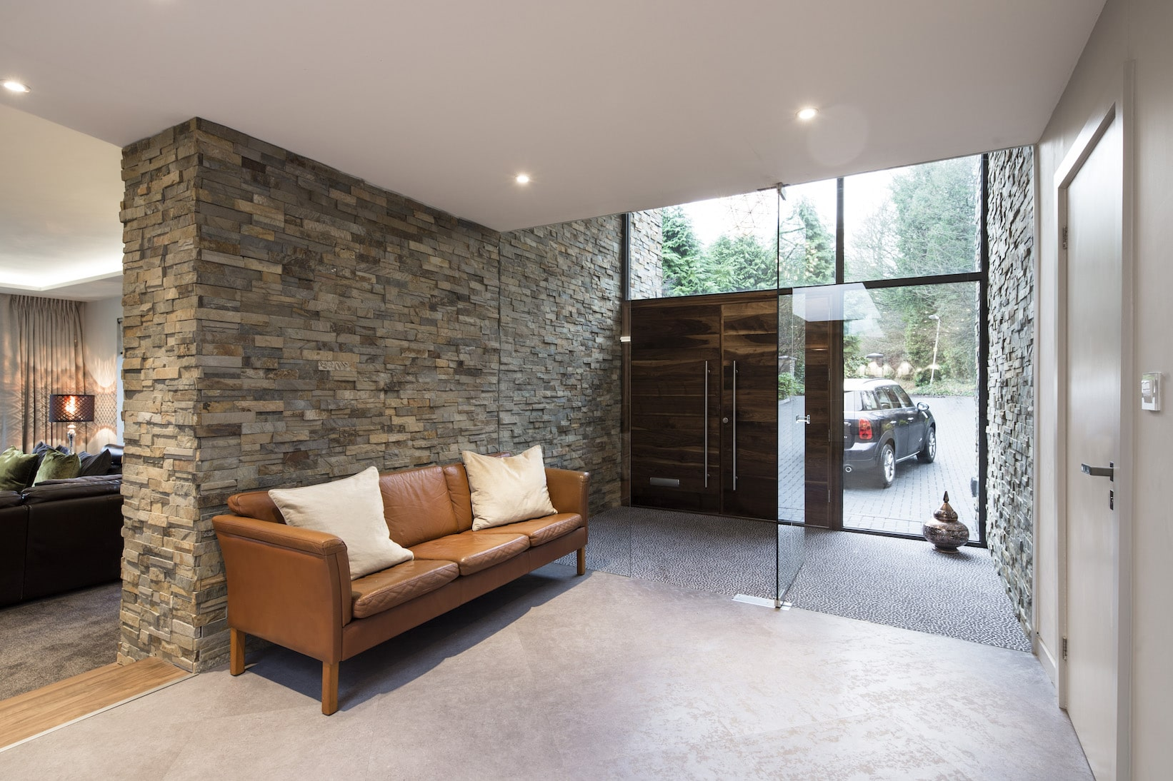 Norstone Ochre Slimline Stone Veneer on a large feature wall in a residential foyer with a floor to ceiling glass vestibule