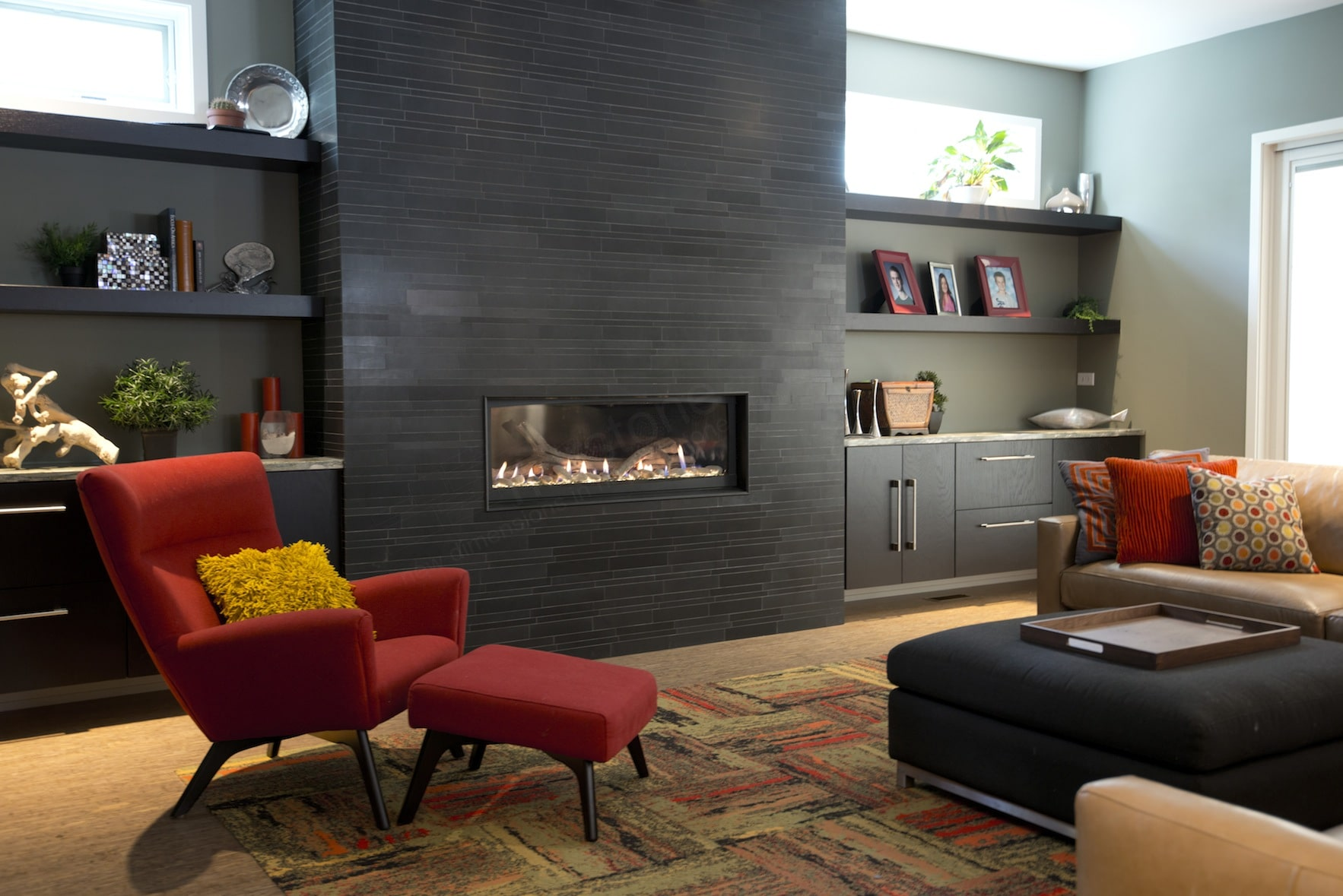 Norstone Natural Stone Veneer Ebony Lynia Interlocking Tile used on a modern fireplace with a contrasting colored red chair