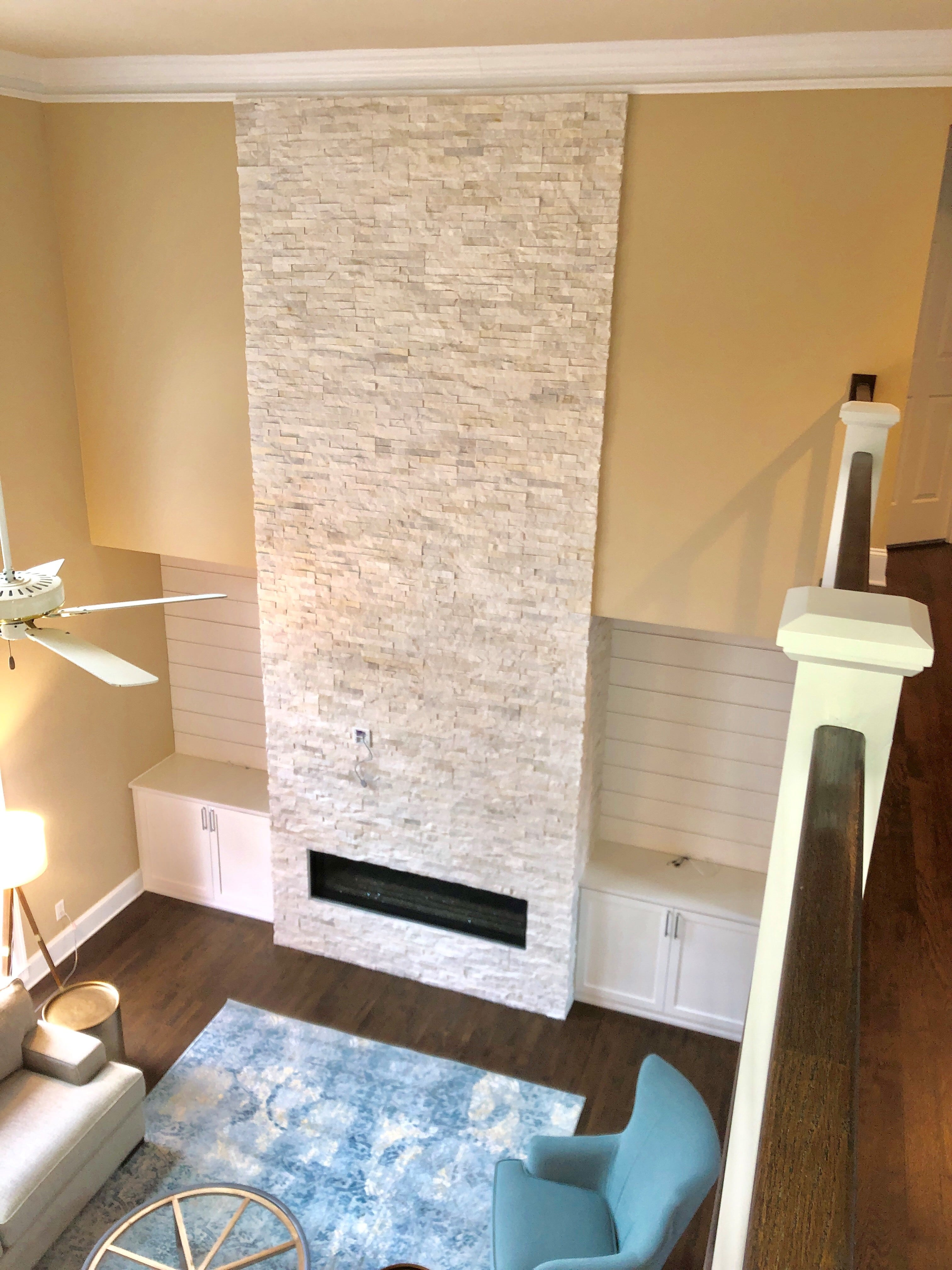 Norstone White Rock Panels used on a two story residential fireplace as seen from an upper stairway looking down