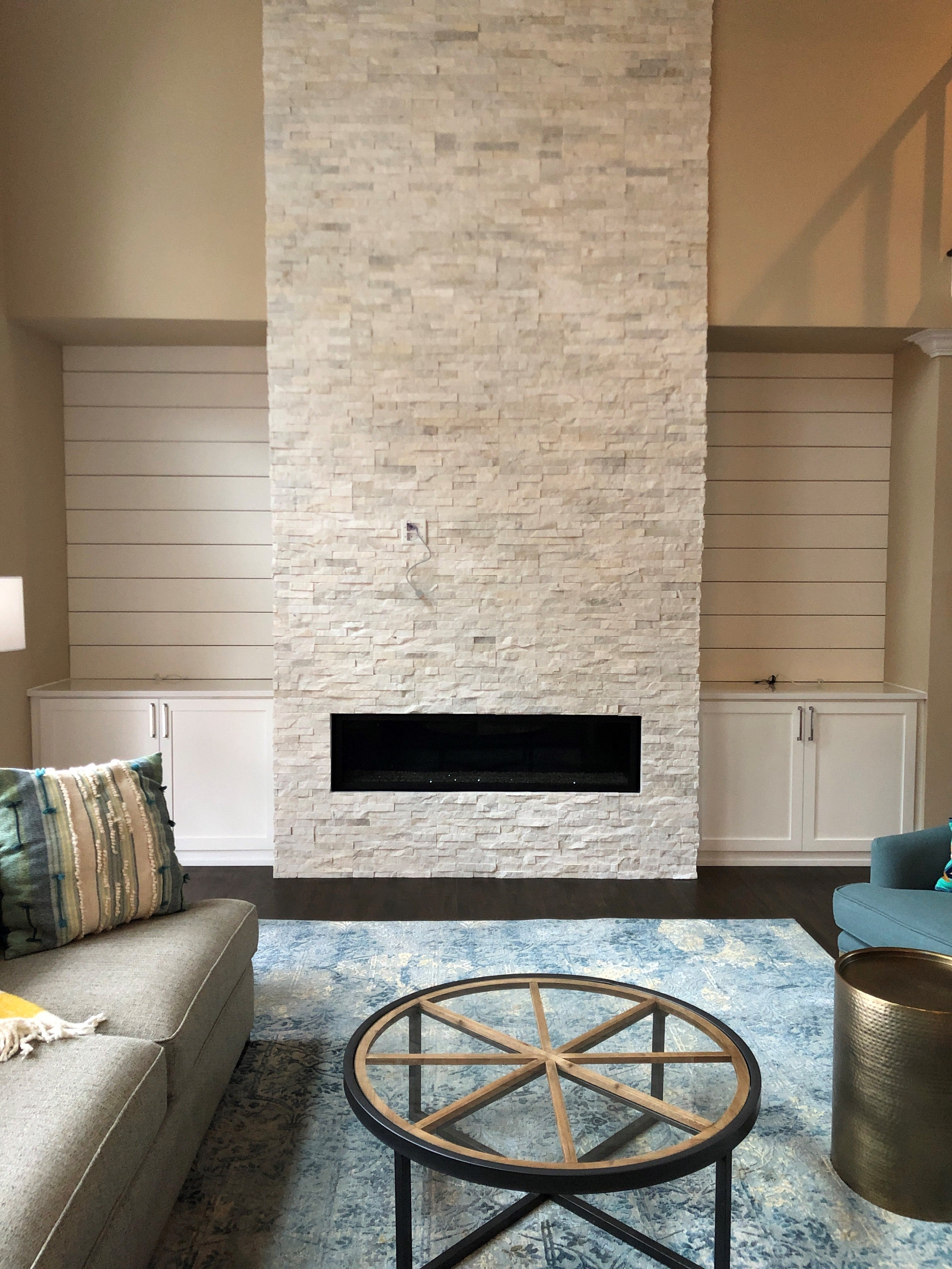 Norstone White Rock Panels used on a two story residential fireplace featuring a long linear fireplace and built in cabinets