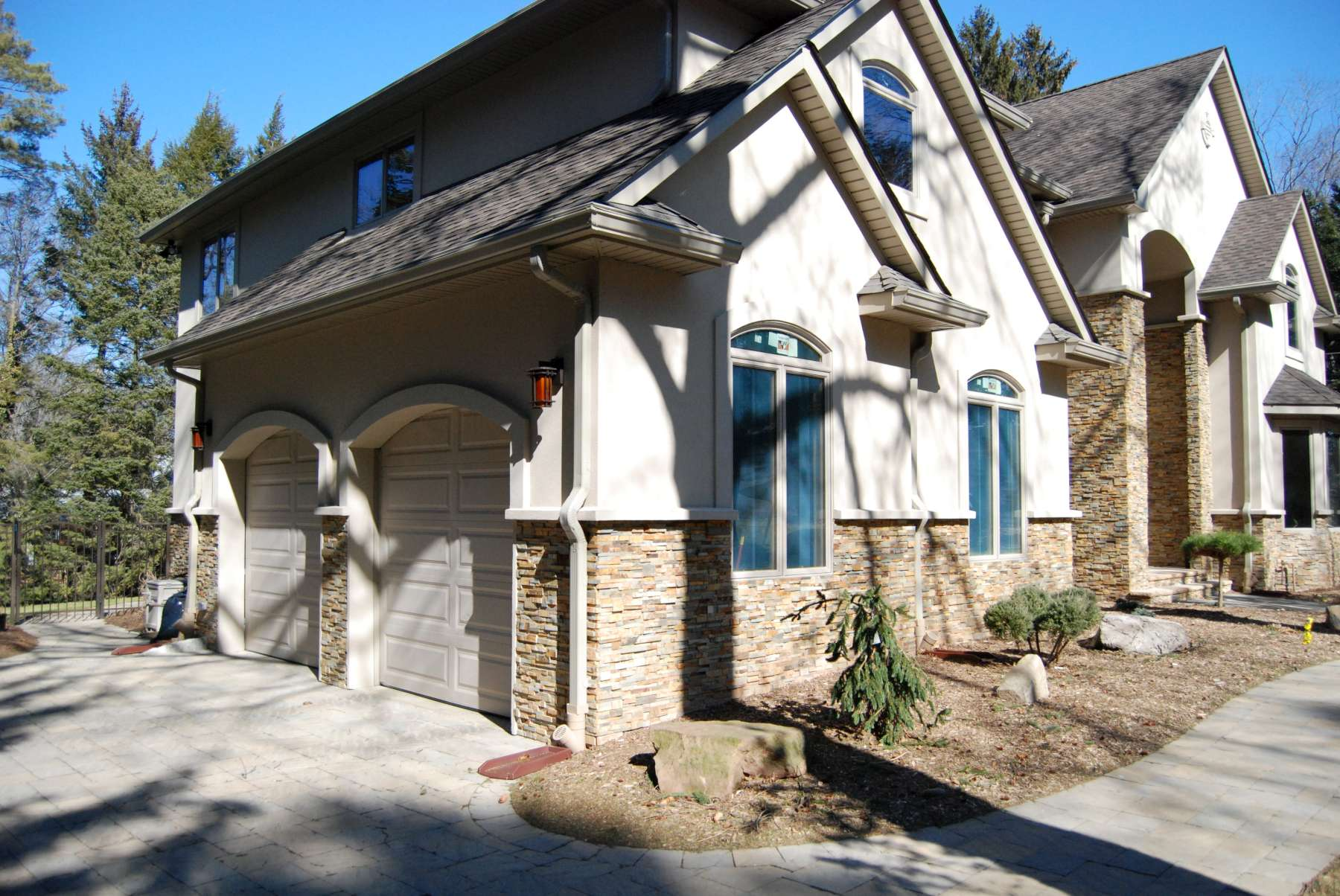 Stone veneer installed over an EIFS system on a residential project with stucco above the stone
