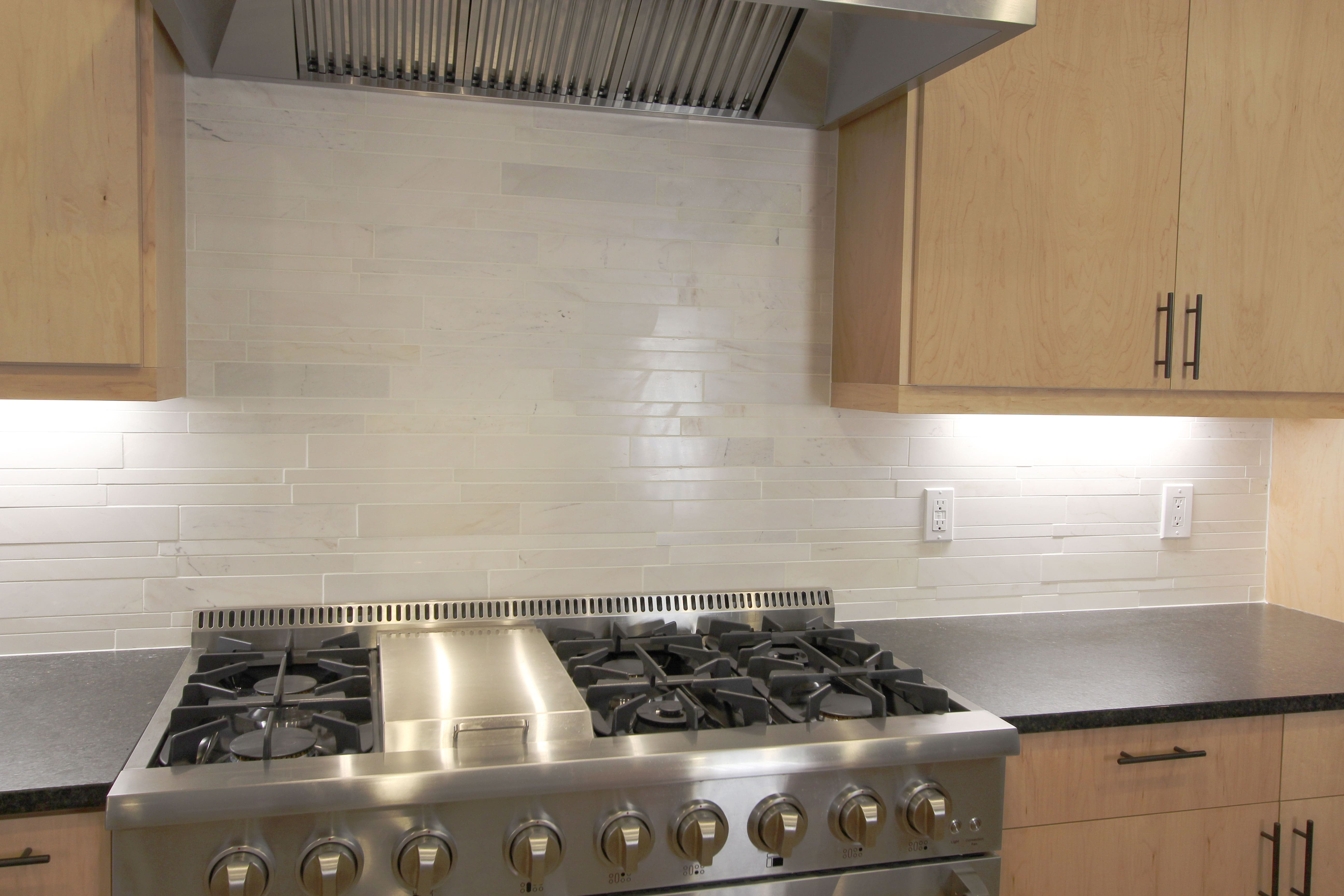 Norstone White Marble Lynia Interlocking Tiles used on a kitchen backsplash set against a large 6 burner stainless steel range and vent hood