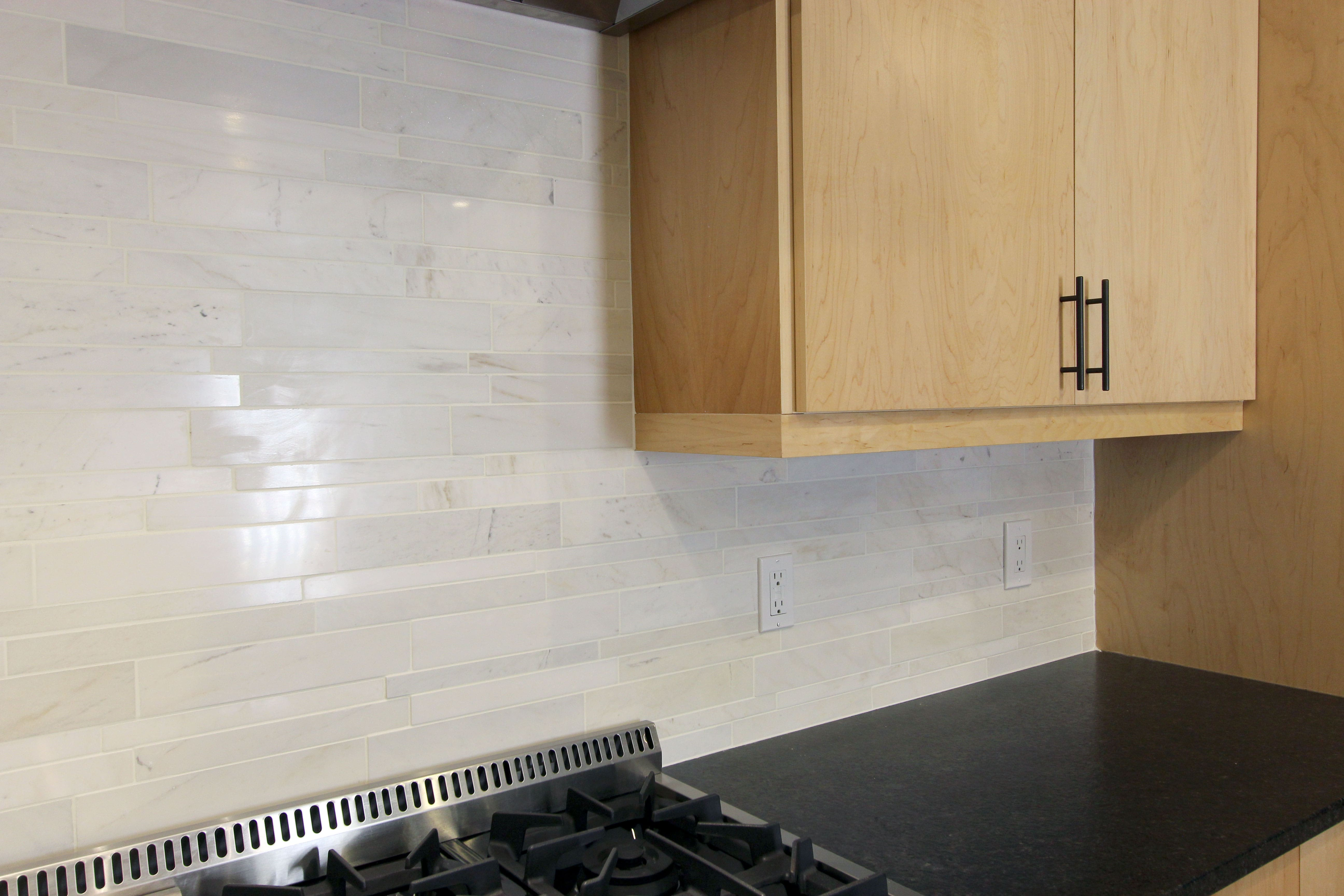 Norstone White Marble Lynia Interlocking Tiles used on a kitchen backsplash showing electric outlets extended out against the tile