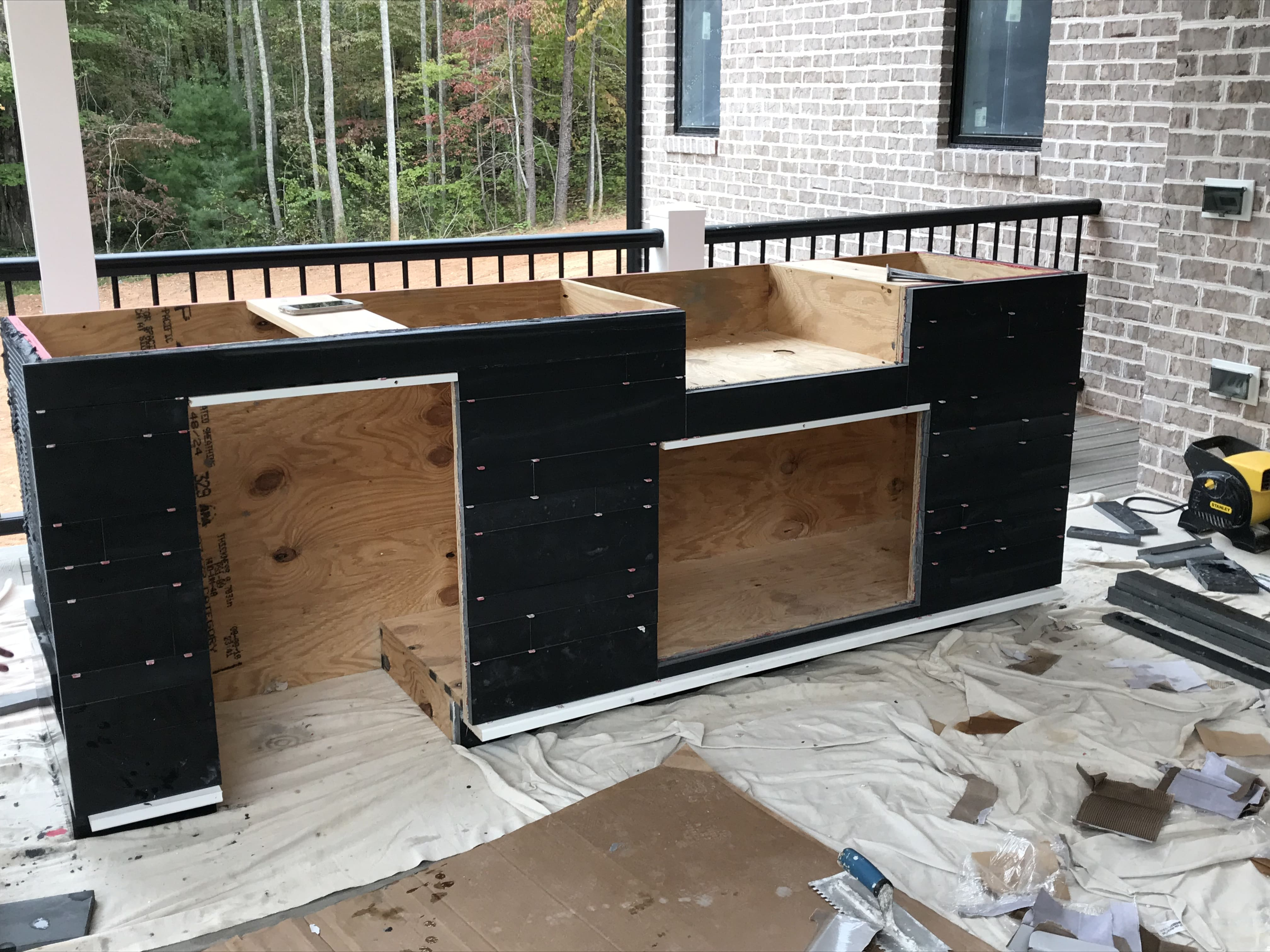 Norstone Ebony Planc Large Format Tile Being installated on a residential outdoor kitchen project