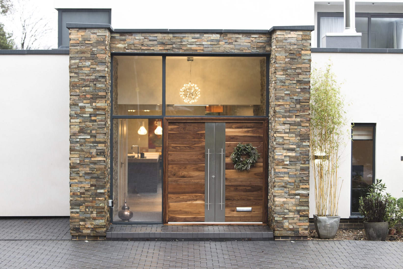 Norstone Slimline Ochre Rock Panels on modern residential entryway with double wooden doors and large glass wall