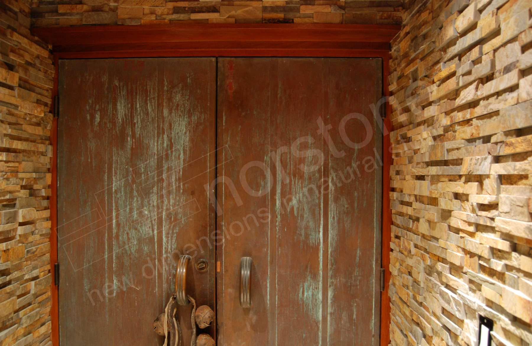 Norstone Ochre Stacked Stone Rock Panels on Entrway to underground Wine Cellar in California with metal rusted doors