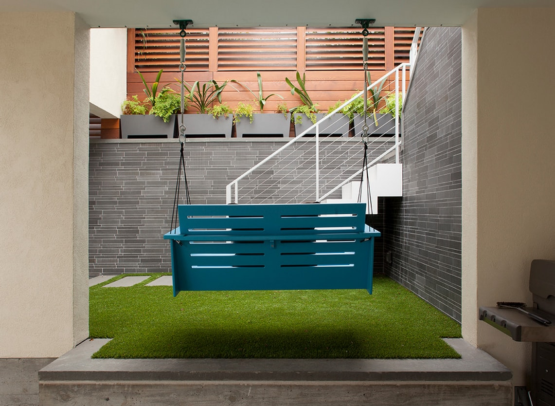 Norstone Grey Basalt Lynia Interlocking Tile Feature Wall in San Francisco Interior Courtyard with Synthetic Turf and a porch swing