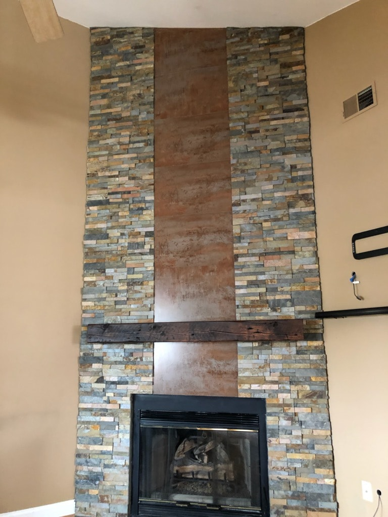 Norstone Ochre Stacked Stone Rock Panels on a corner fireplace with vertical metal insert from floor to ceiling